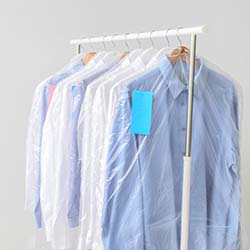 Rack with clothes after dry-cleaning on light background